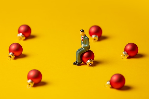 Miniature figure of man sits on christmas bauble on yellow surface
