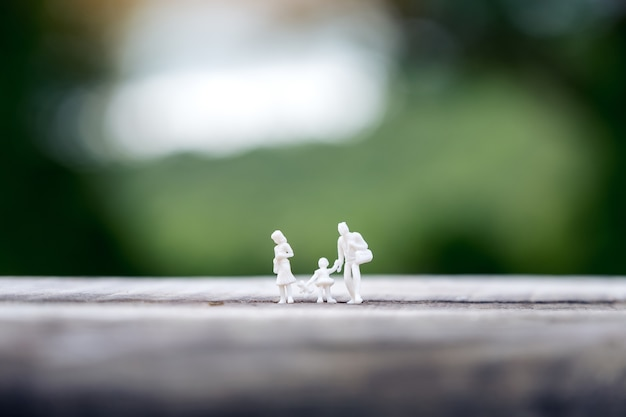 Miniature figure model of father , mother and daughter walking together on wooden table