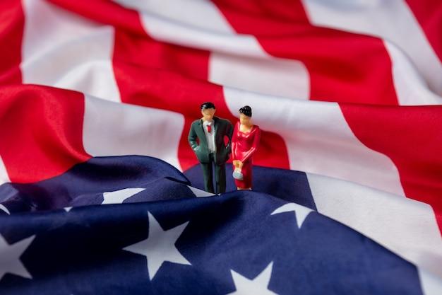 Миниатюрная фигура женщин и мужчин-политиков на флаге сша