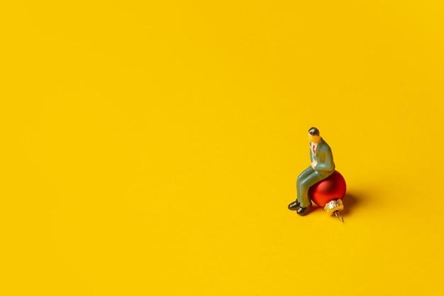 노란색 배경에 크리스마스 값싼 물건에 앉아 있는 남자의 미니어처 그림
