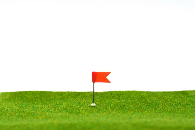 Miniature figure of red flag at the golf course and putting green or artificial green lawn