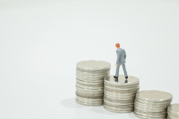 Miniature figures businessman walking to top of stack of coins