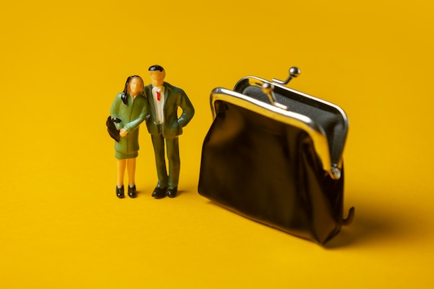 Miniature figures of a man and woman next to classic wallet on yellow surface