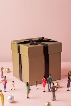 사람의 미니어처 피규어와 큰 선물 상자
