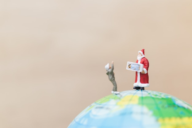 Miniature figures of santa claus holding gift for kids