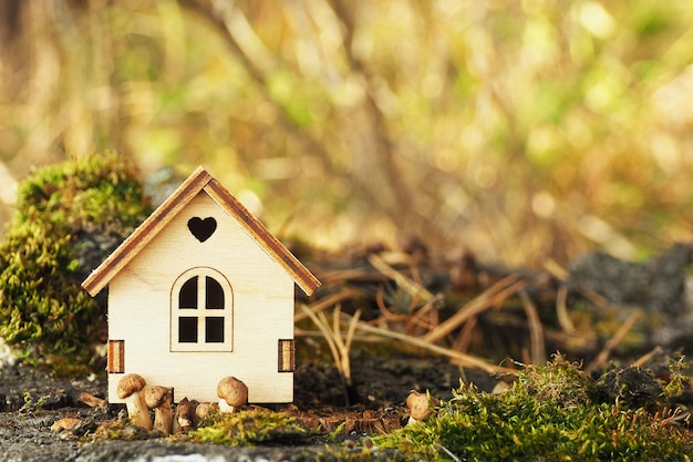 A miniature figurine of a wooden house on a birch stump with moss and small mushrooms.