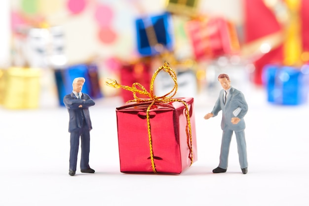 빨간 크리스마스 선물을 가진 두 사업가의 미니어처 인형