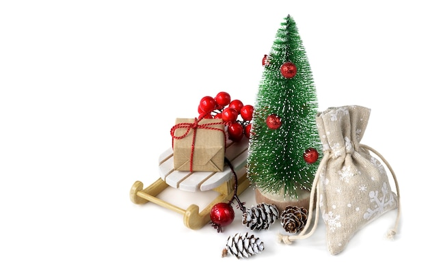 흰색 배경에 고립 썰매에 크리스마스 선물 미니어처 전나무 나무.