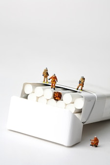 Miniature firefighters and cigarettes on white background