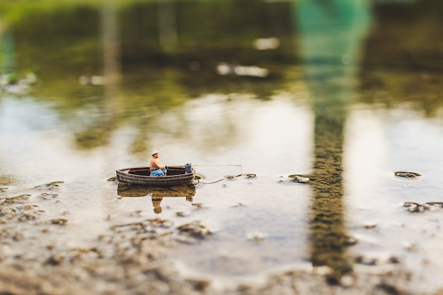 Miniature fishermen are fishing by boat