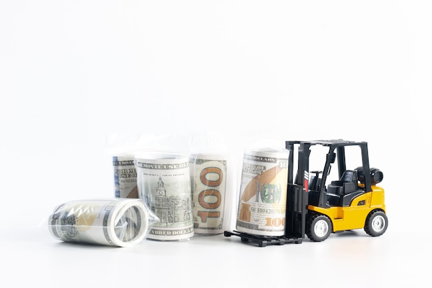 Miniature forklift loading dollar bill wrapped in plastic isolated