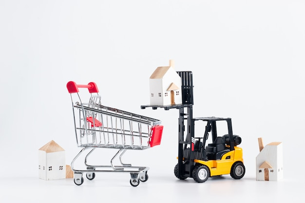 Miniature forklift truck model loading cargo house to red shopping cart isolated on white background