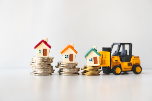 Miniature forklift vehicle lifting miniature house on stack coins