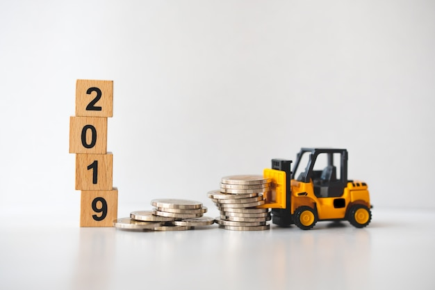 Miniature forklift vehicle working on stack coins on wooden block year 2019 background