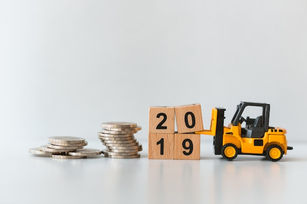 Miniature forklift vehicle working on stack coins on wooden block year 2019