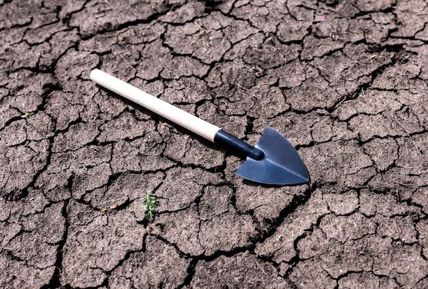 乾燥した土壌のミニチュアガーデンツール。庭のコンセプト。
