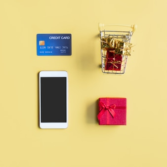 Miniature of gift boxes in trolley, credit card and smartphone on yellow background