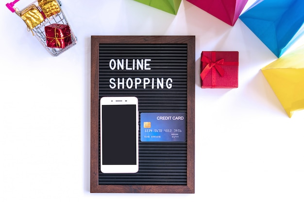 Miniature of gift boxes in trolley, smartphone, word on black frame, credit card and colorful bags on white desk. online shopping, technology and lifestyle concept.