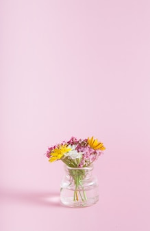 Miniature glass bottle with wildflowers on a pink background copy space for congratulations on march 8, easter, mother's day vertical format