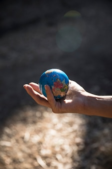Miniature globe in hand in nature