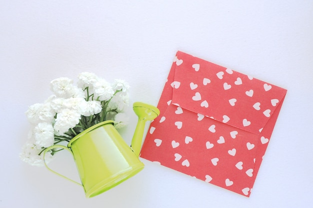 A miniature green watering can with a bouquet of white flowers and an envelope with hearts lie on a white table.