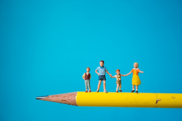 Miniature group of children standing on yellow pencil using as family and education concept