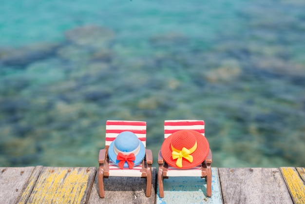 Miniature hats on beach chair with sea background. vacation concept.