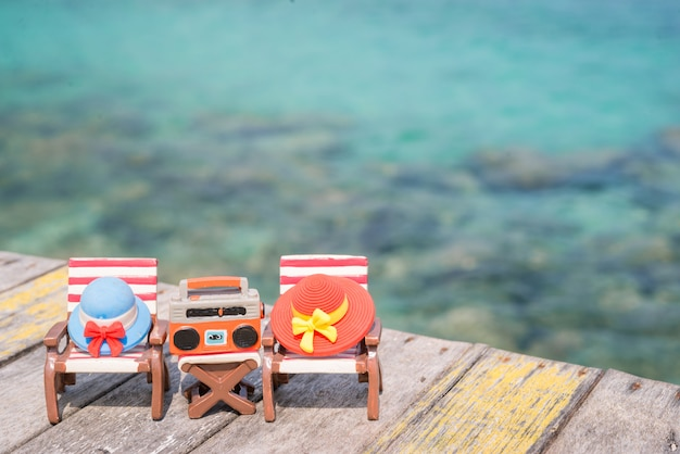 Miniature hats on beach chair with sea background.