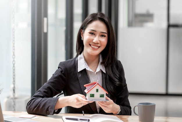 Miniature house in the hands of an asian woman real estate agent home loan working at the office. looking at the camera.
