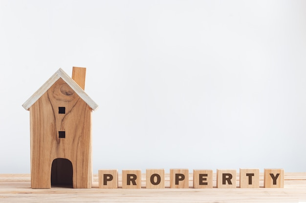 """Miniature house and letter """"property"""" on wooden alphabet blocks on wood floor with copyspace in property investment"""