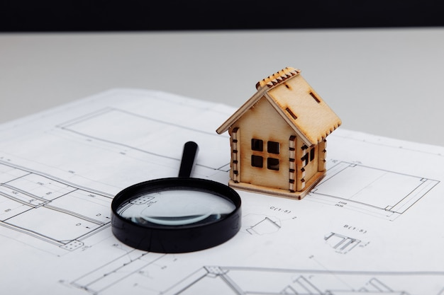 Miniature house and a magnifying glass on a drawing real estate building concept