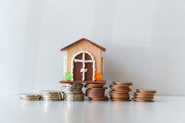 Miniature house with pile coins on white background