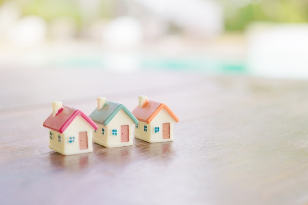 Miniature house on wooden background