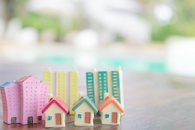 Miniature house on wooden background.