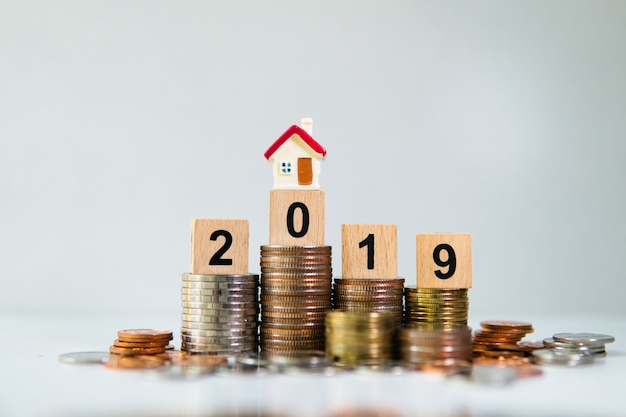 Miniature house on wooden block year 2019 with stack coins