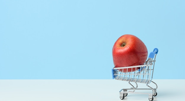 Miniature iron shopping cart with an apple on a blue background. healthy food, food delivery, copy space