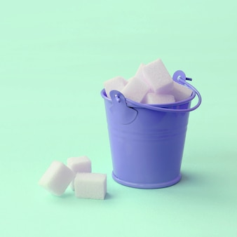 A miniature lilac bucket filled with cubes of sugar lies on a turquoise pastel