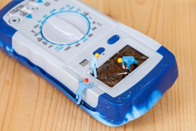 Miniature maintenance team repairing a broken digital multi meter.
