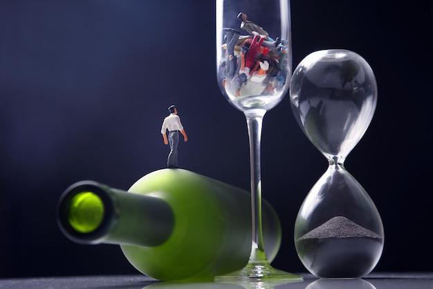 アルコール中毒のミニチュア男がガラスの背景にボトルの上を歩いている