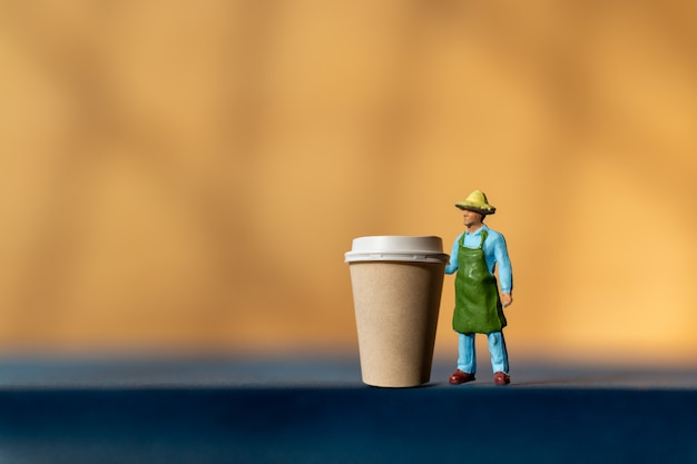 Miniature man and coffee to-go cup