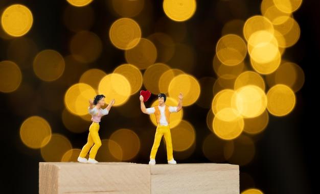 Миниатюрный человечек на деревянном кубике держит красное сердце для любовника с желтыми огнями