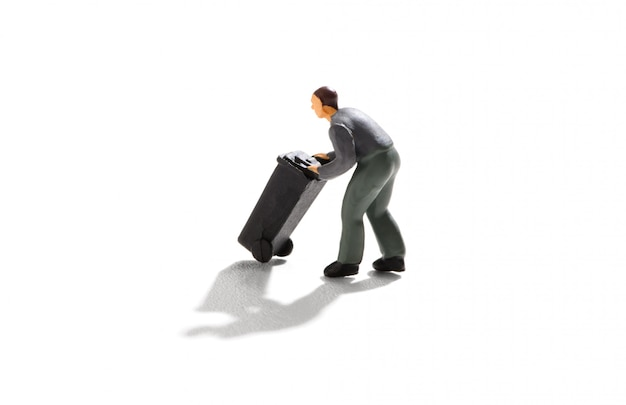 Миниатюрный мужчина толкает черную мусорную корзину