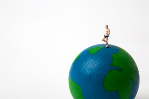 Miniature man running on globe on white