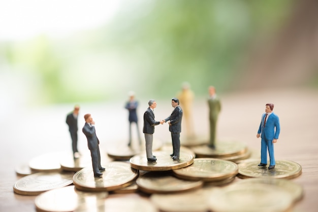 Miniature man standing on coins