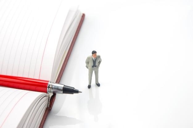 白い背景に大きなノートとペンを持つミニチュア男