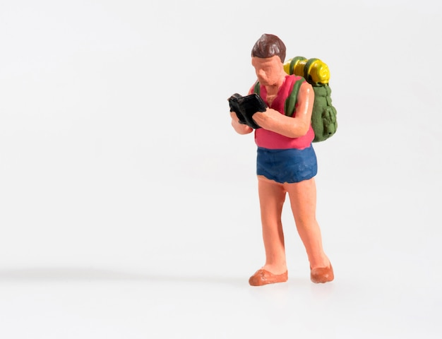Miniature man with a map trekking on vacation