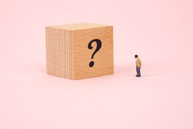 Miniature man with question mark on wood cube