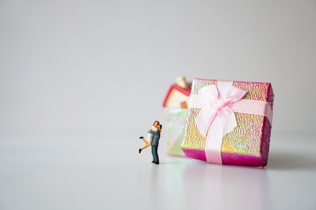Miniature man and woman hug each other on mini house in presents box using as family and property concept
