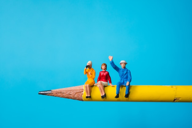 Miniature man and woman sitting on yellow pencil using as business and social concept