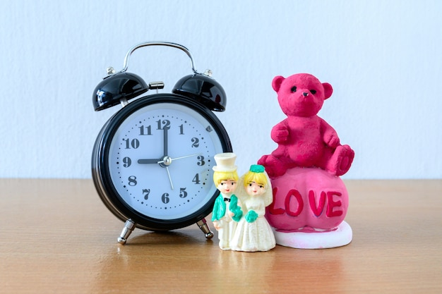 Miniature married couple and teddy bear and clock on wooden. concept for wedding & valentine day.
